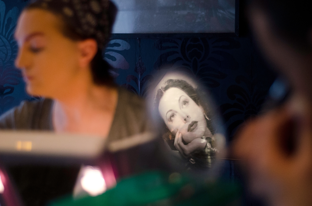 Tim Johnson (left) and his friend, who goes by the drag name of Anita Manhattan, prepare for a drag brunch at Woody's nightclub on February 16, 2014. A photograph of an old Hollywood star on the wall of the dressing room is reflected into Manhattan's makeup mirror.