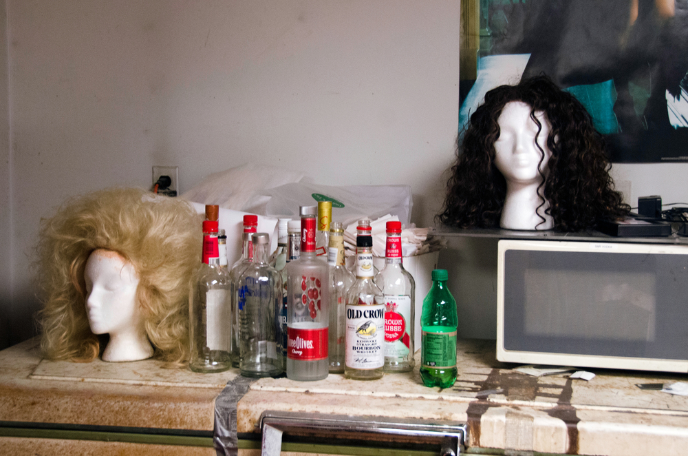 Wigs are seen alongside empty liquor bottles in a dressing room reserved for one of Tim Johnson's drag gigs on April 23, 2014.