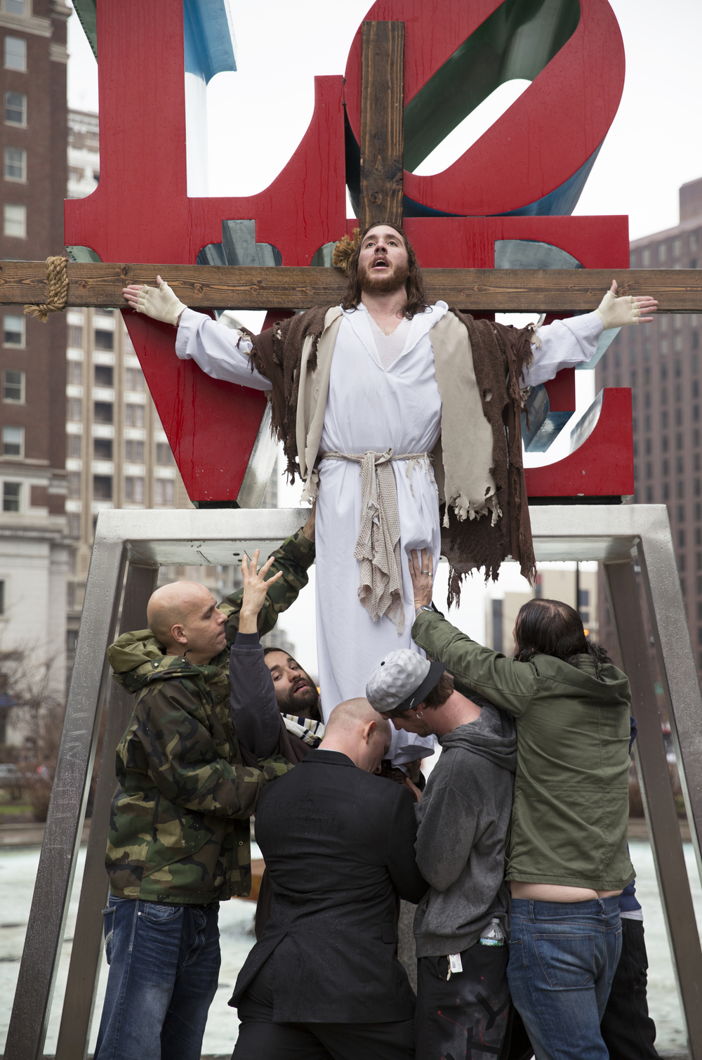 "Michael ""Philly Jesus"" Grant (center) is held up by ""disciples"" in front of Philadelphia's Love Park statue on April 3, 2015. This demonstration was a part of Grant's annual ""Cross Walk,"" in which he and a group of his supporters carry large wooden crosses throughout the city in honor of Black Friday."