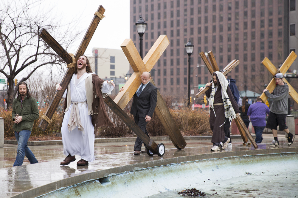 """Michael """"Philly Jesus"""" Grant (second to left) conducts a portion of his Black Friday """"Cross Walk"""" in Philadelphia's Logan Square on April 3, 2015. The Cross Walk is an annual event in which Grant and a group of his supporters carry large wooden crosses throughout the city."""