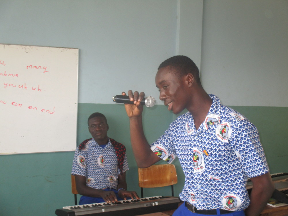 A photograph of Josh singing (and other Josh playing the keyboard) at graduation rehearsal, by  Osman, Class 6.
