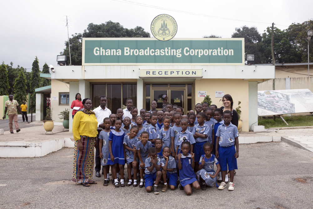Madame, Hayford, Cornelius, and Mariana stand with the kids in front of the Ghana Broadcasting Corporation.