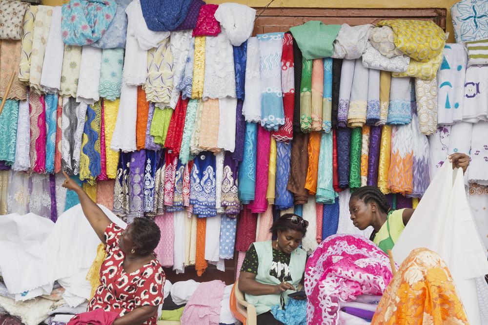 Women sell fabric at Makola Market.