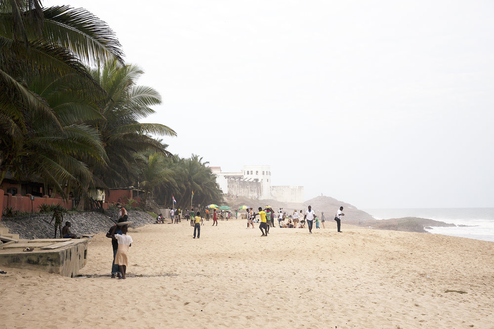 A faraway view of Cape Coast Castle from the beach in front of Oasis