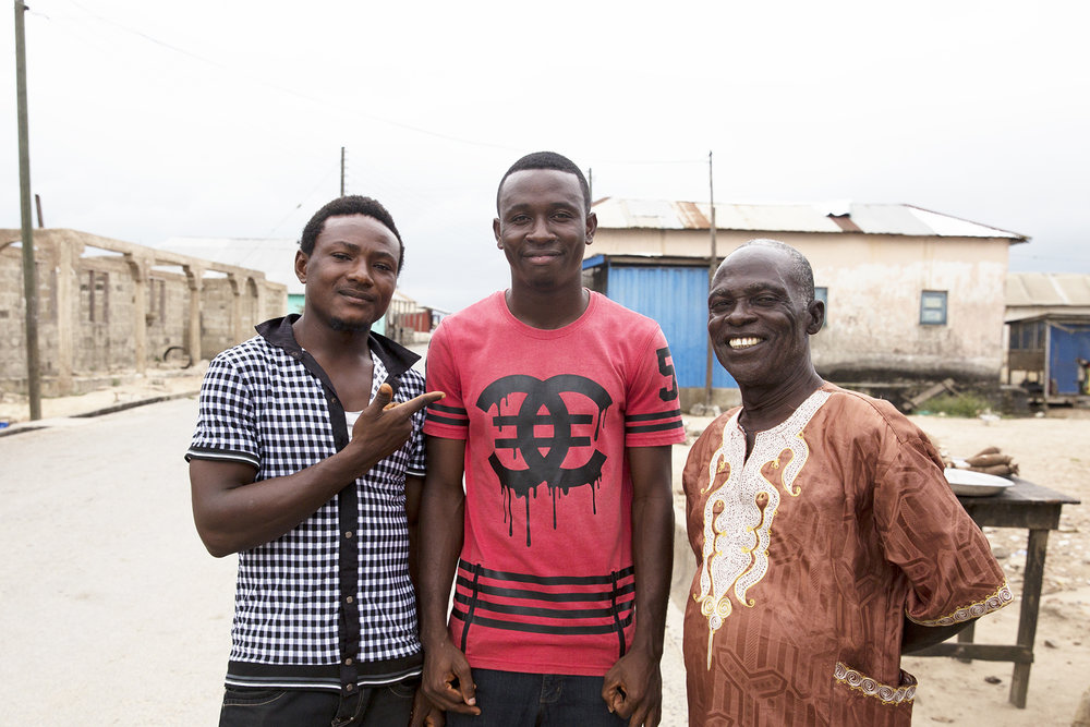 Francis stands on the street with Allahassan (left) and Abubakal (right)