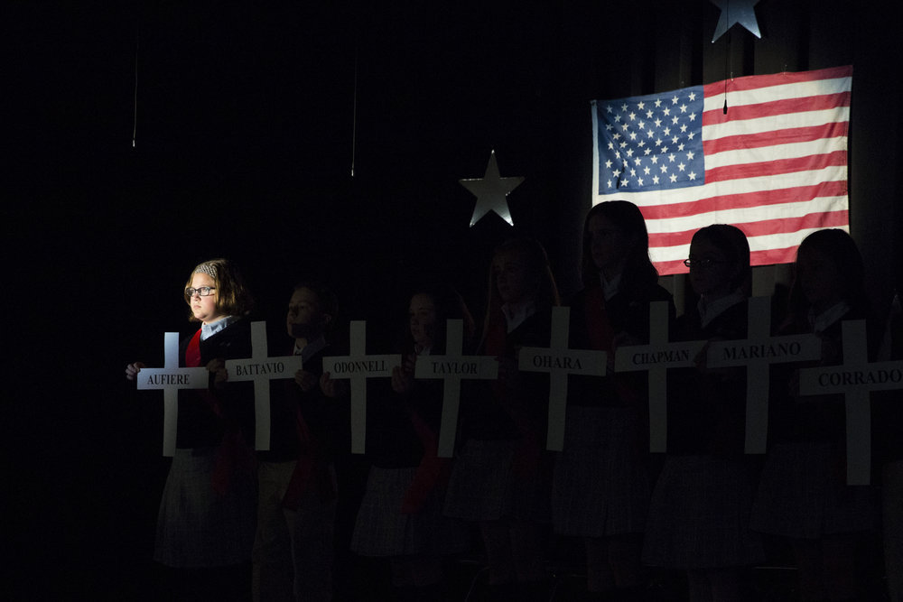 Sixth-grade students at Mater Dei Catholic School hold up crosses proclaiming the names of deceased servicemen whom are buried in the St. Stanislaus Parish Cemetery.   ©  Montgomery Media