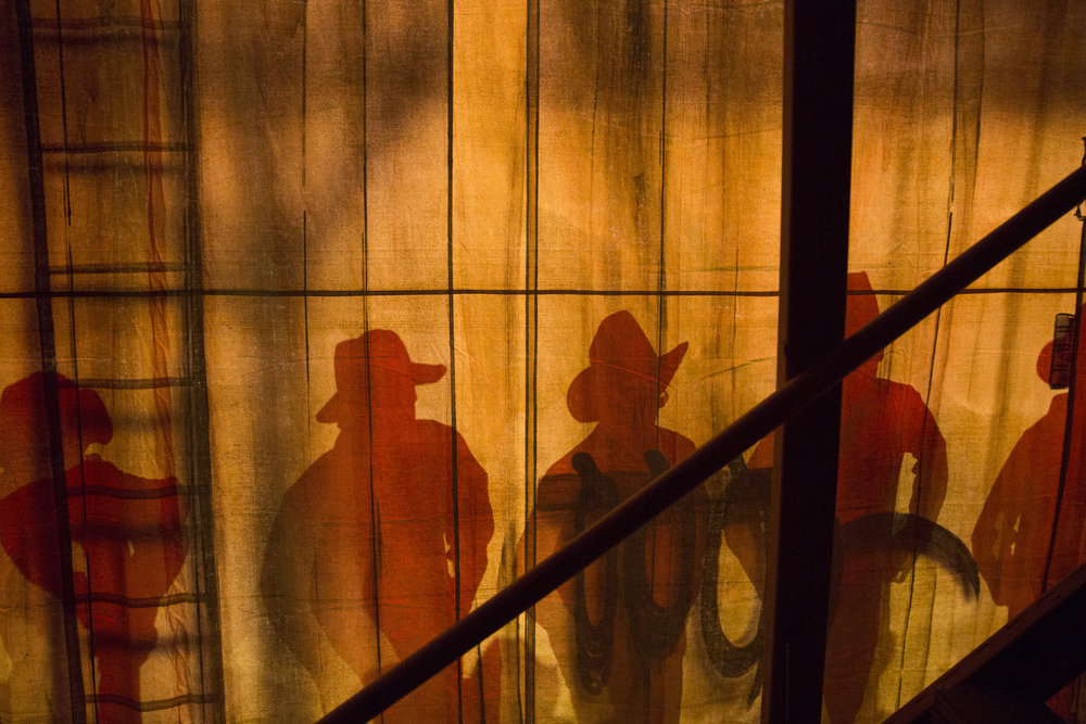 At a dress rehearsal for Archbishop Wood High School's production of Footloose: The Musical, cast members are silhouetted as viewed from backstage. ©Montgomery Media