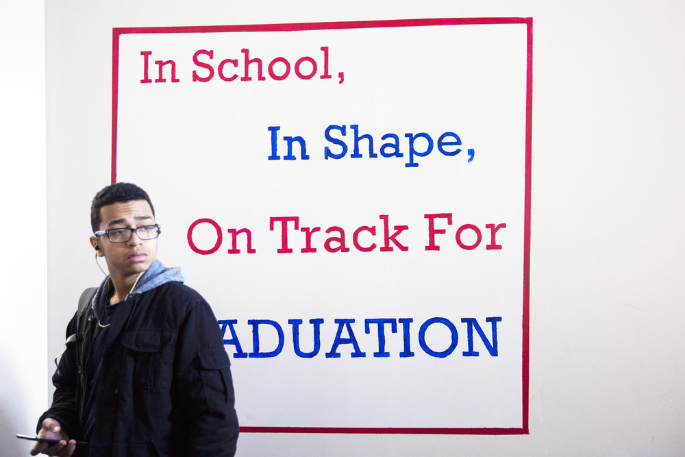 "Johnathan Hernandez pauses at the entrance to SquashSmarts, which displays the program's motto: ""In school, in shape, on track for graduation."" Johnathan is going into the ninth grade and has been with the program for one year."