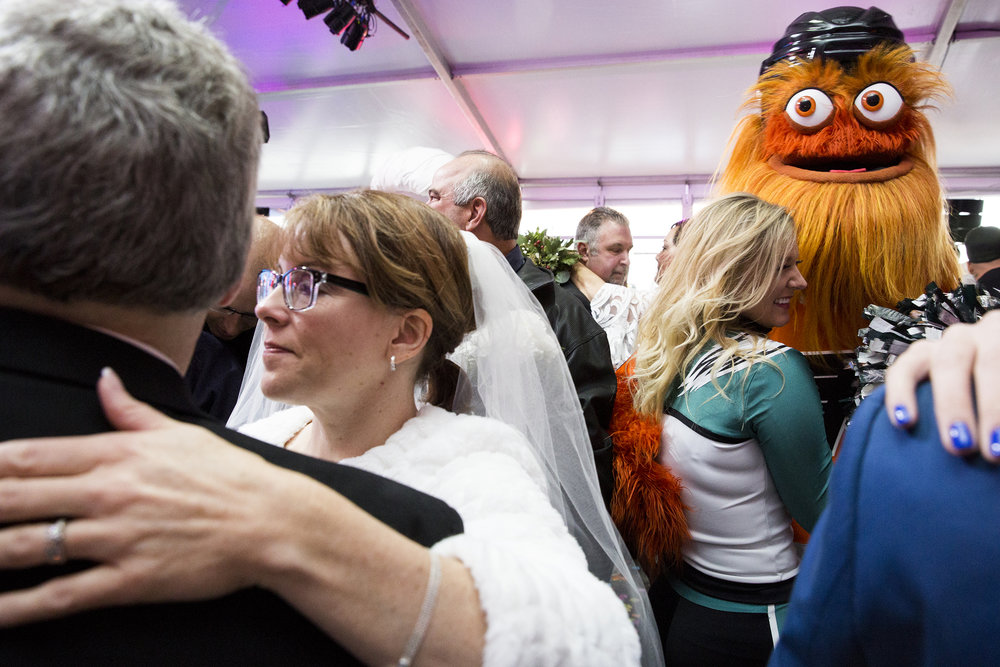 Gritty (right), the beloved mascot of the Philadelphia Flyers hockey team, ordains a mass wedding of over sixty couples at the Preston and Steve Show's Camp Out For Hunger on November 28, 2018. (On assignment for Chorus Media Group)