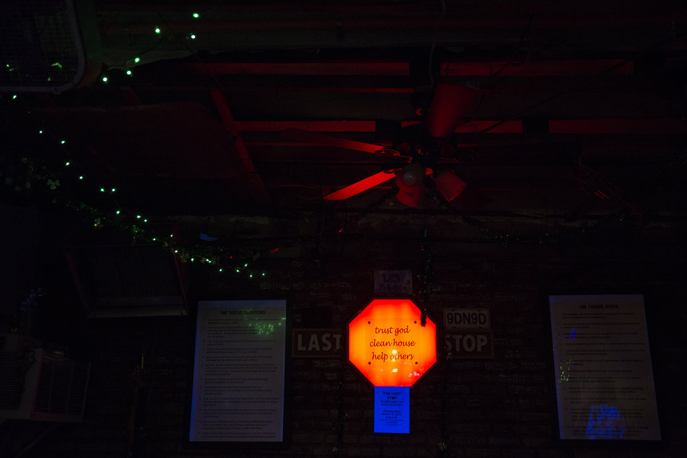 "A neon sign in the main room of The Last Stop reads, ""trust god / clean house / help others."""