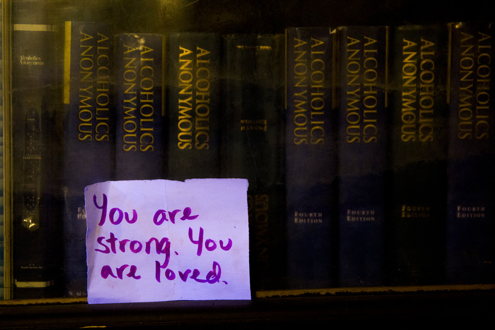 "A sign reading ""You are strong. You are loved."" sits in front of a shelf of Alcoholics Anonymous bibles at The Last Stop on February 17, 2019."