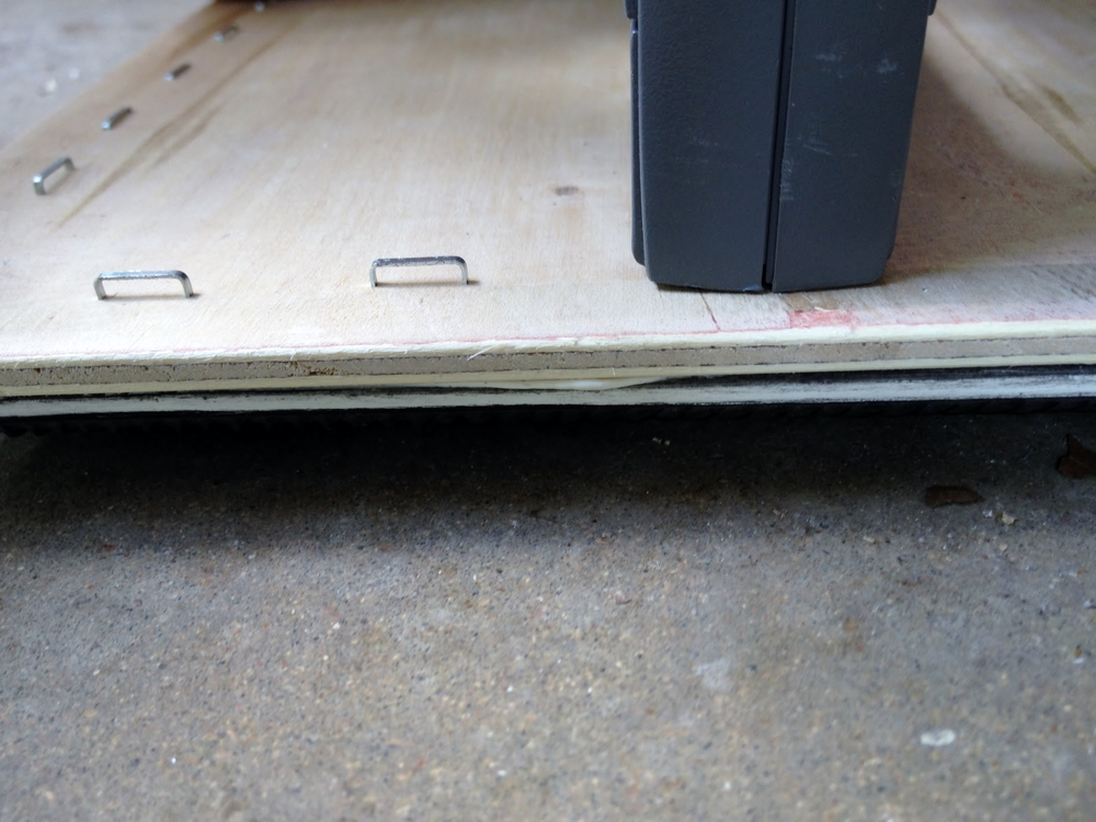 Wipe off excess adhesive as you staple. Notice the staples are not flush with the plywood...