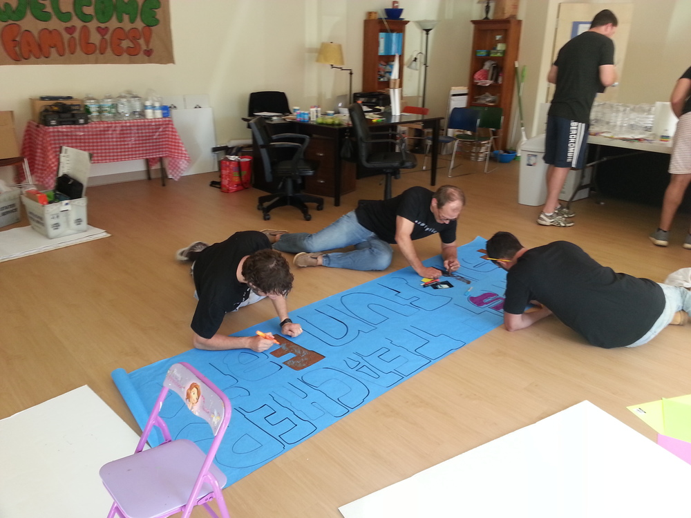 Volunteers from Adelphic Mobile help First Teacher prepare for a family oriented event to encourage parents to take an active role in their children's early education