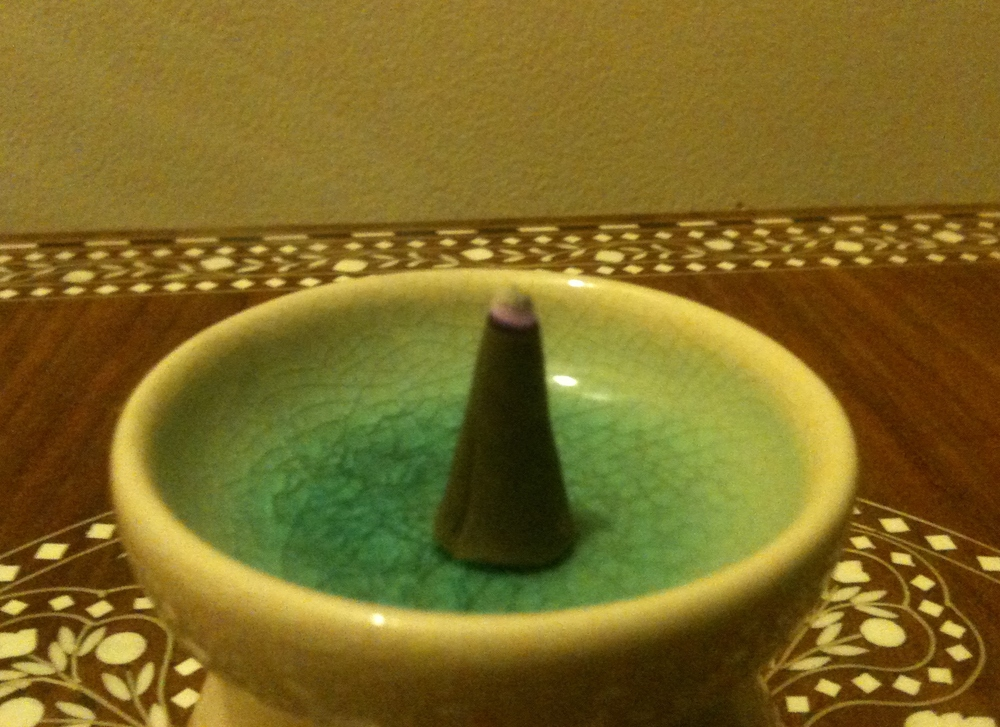 A burning lavender sandalwood incense cone from Thailand
