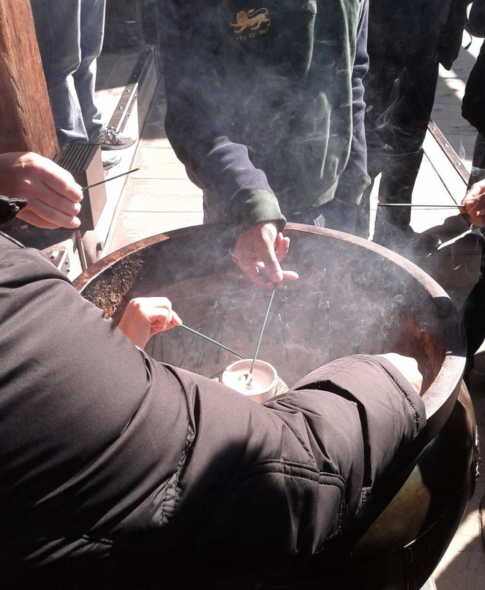 Burning incense at the Kiyomizu temple in Kyoto, Japan