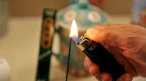 Lighting an incense stick with a lighter