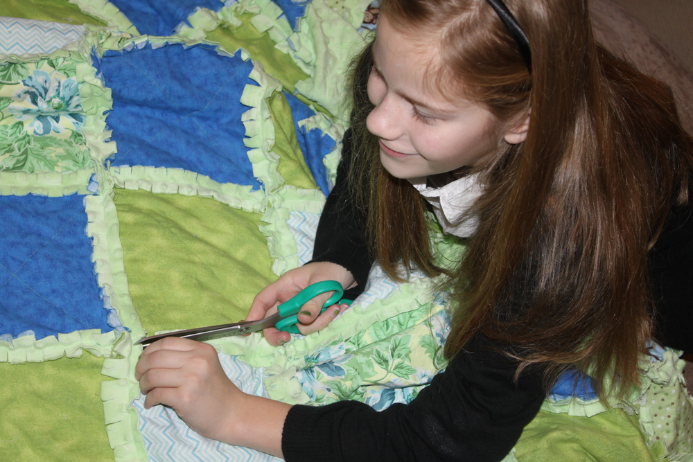 Jessie cutting her rag quilt.