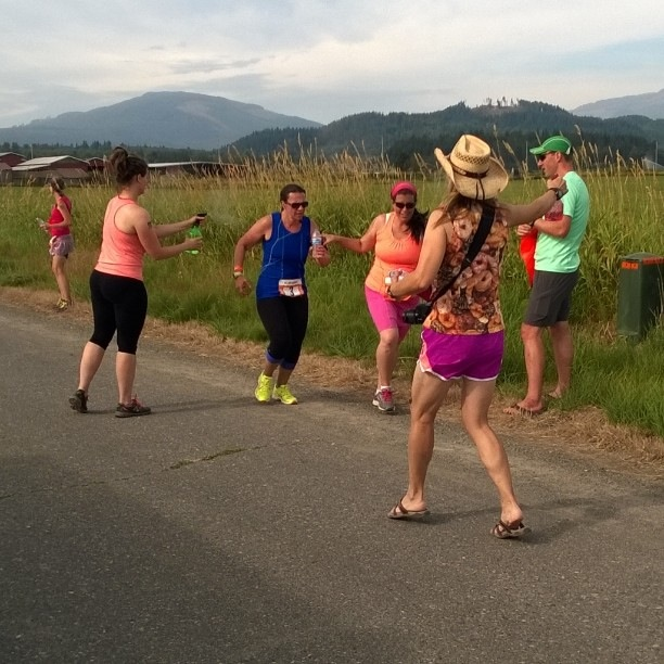 Spraying Sandra down with squirt bottles.  (look at those runner calves on that gal  with a cowboy hat on!)