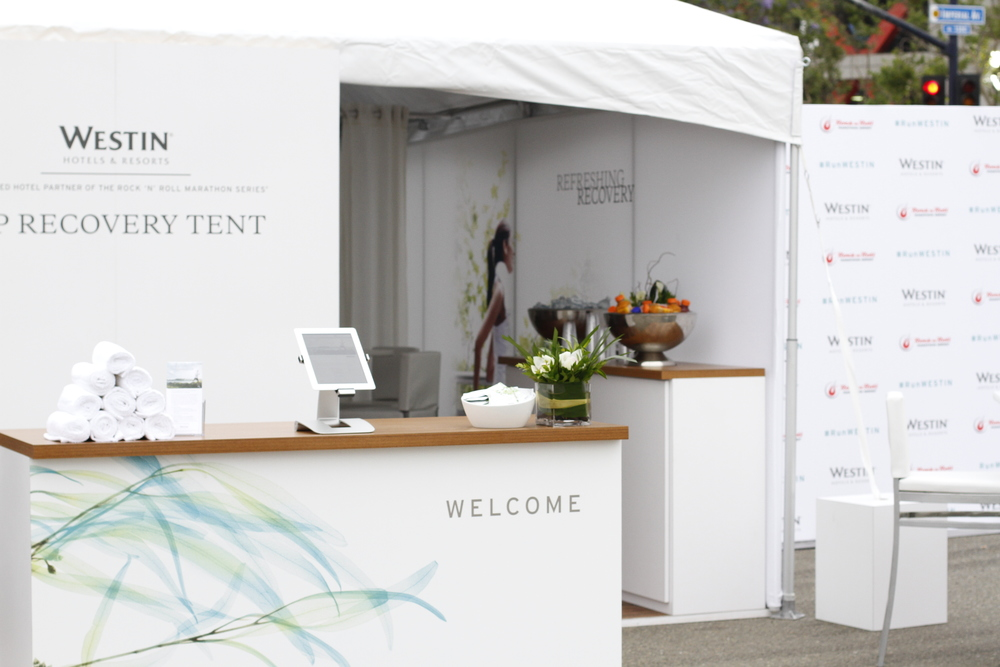 The RunWESTIN Concierge congratulates guests as they cross the finish line and directs them to the Westin VIP Recovery Tent.