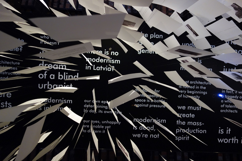 "A view from the floor of the Latvian pavilion. The sheets of paper carry images of Modernist buildings; the ceiling asks, ""There is no Modernism in Latvia"", commenting on the lack of historical scholarship. Courtesy NRJA"