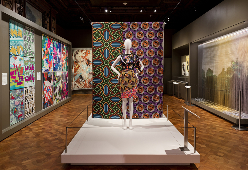 The exhibition's Intricate section includes Dutch wax prints from Vlisco (foreground) and a custom tapestry from Colombian weaving atelier Hechizoo (pictured right).