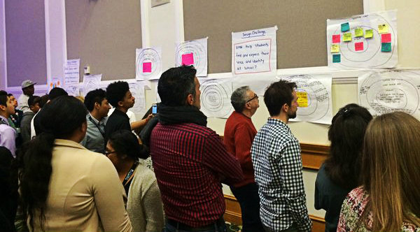 Participants at Big Ideas Fest exploring a wall of design challenge solutions