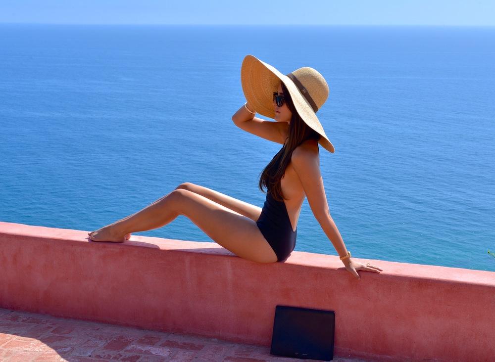 Mandana is wearing a Hermès halter bathing suit, Hermès ceramic bangle, Christian Dior sunglasses, gold Rolex watch, Céline attaché Photo by Yuliia Barbashova