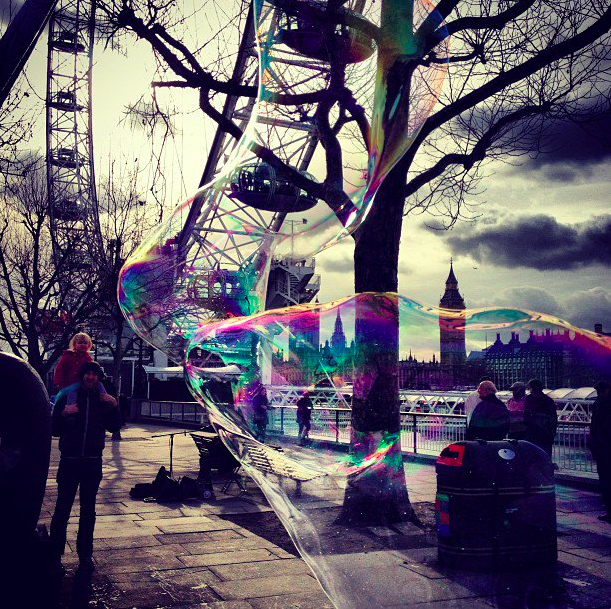 Some kids are blowing bubble balloons- A view of the London Eye.