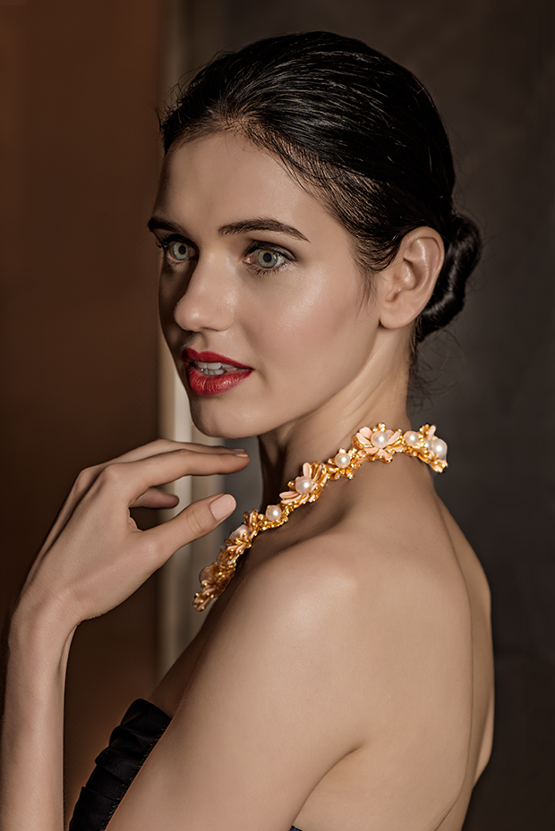 Our eyes go right to the beautiful pearl and gold necklace - by design.