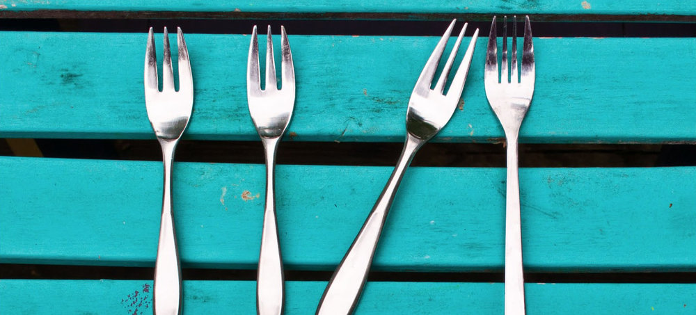 Four identical forks, aligned side-by-side, and the second one from left-to-right is tilted diagonally to look out of place