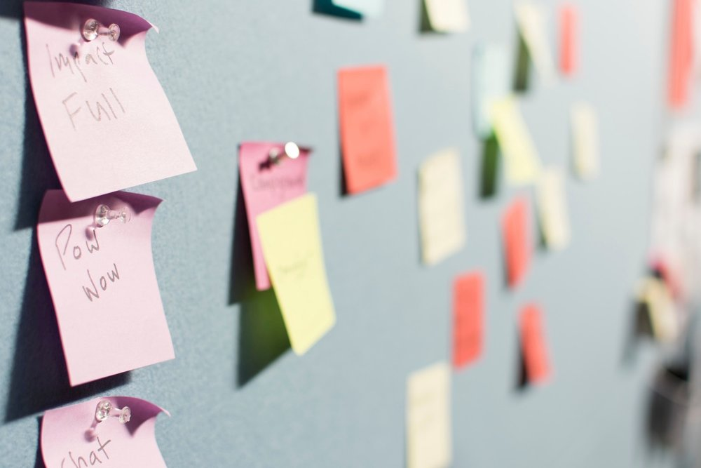 "Photo by  Patrick Perkins  on  Unsplash . A wall filled with post-its of different colors. The two closest post-its to the left are pink and have it written on them ""Impact Full"" and ""Pow Wow""."