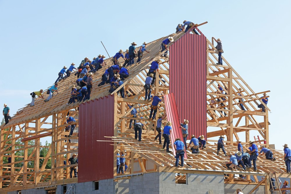 Photo by  Randy Fath  on  Unsplash . Amish barn-raising with dozens of people working on the structure.