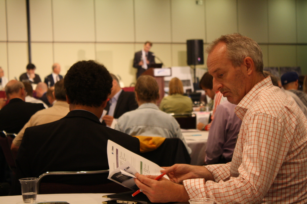 An attendee reading the material, while Dave Dilks delivers an opening address.