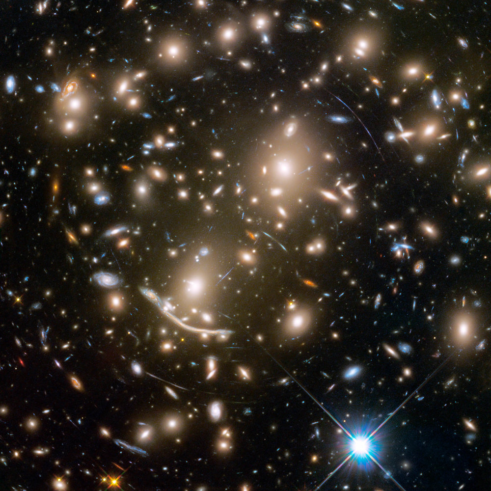 A galaxy cluster acts like a giant lens, distorting and magnifying the light from distant galaxies.