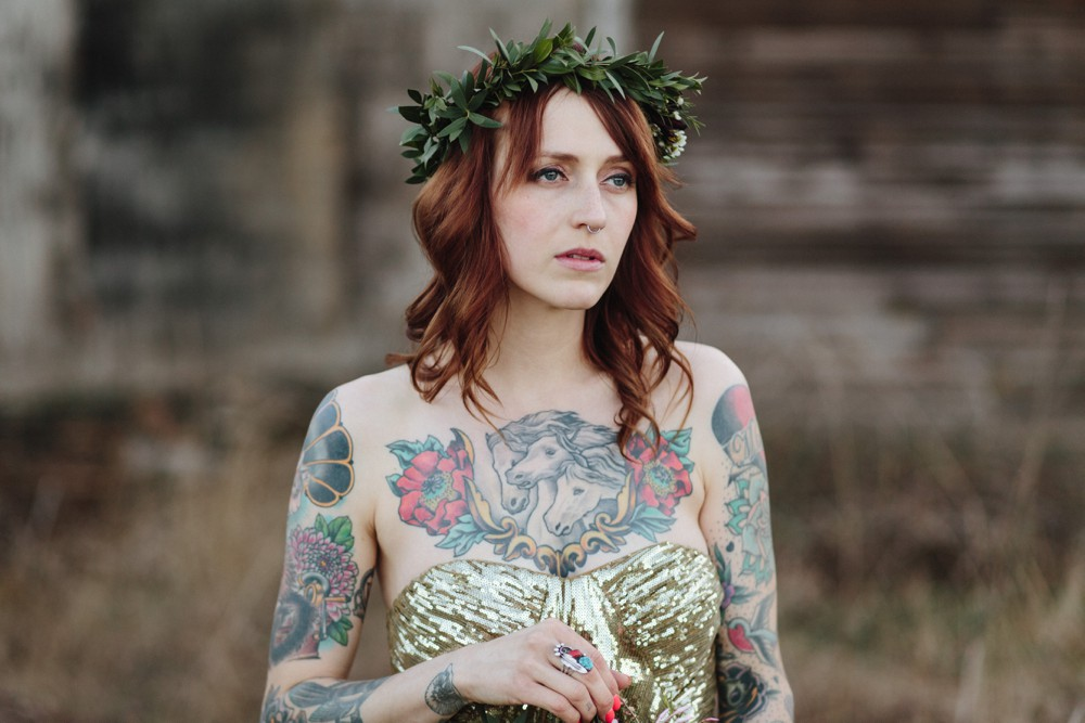 A tattooed bride in a gold wedding dress.