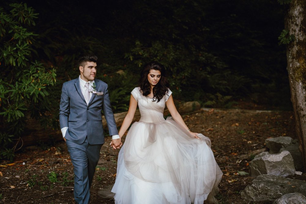 The bride and groom walk together in the Portland Rose Garden by photographer Catalina Jean