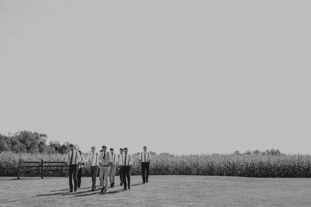 Groomsmen walking in a field at a barn wedding by photographer Catalina Jean