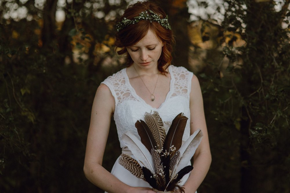 Brides holds a wedding bouquet made of feathers