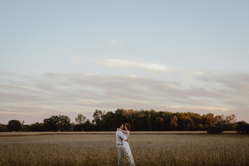 Bride and groom portrait in a field by Catalina Jean Photography