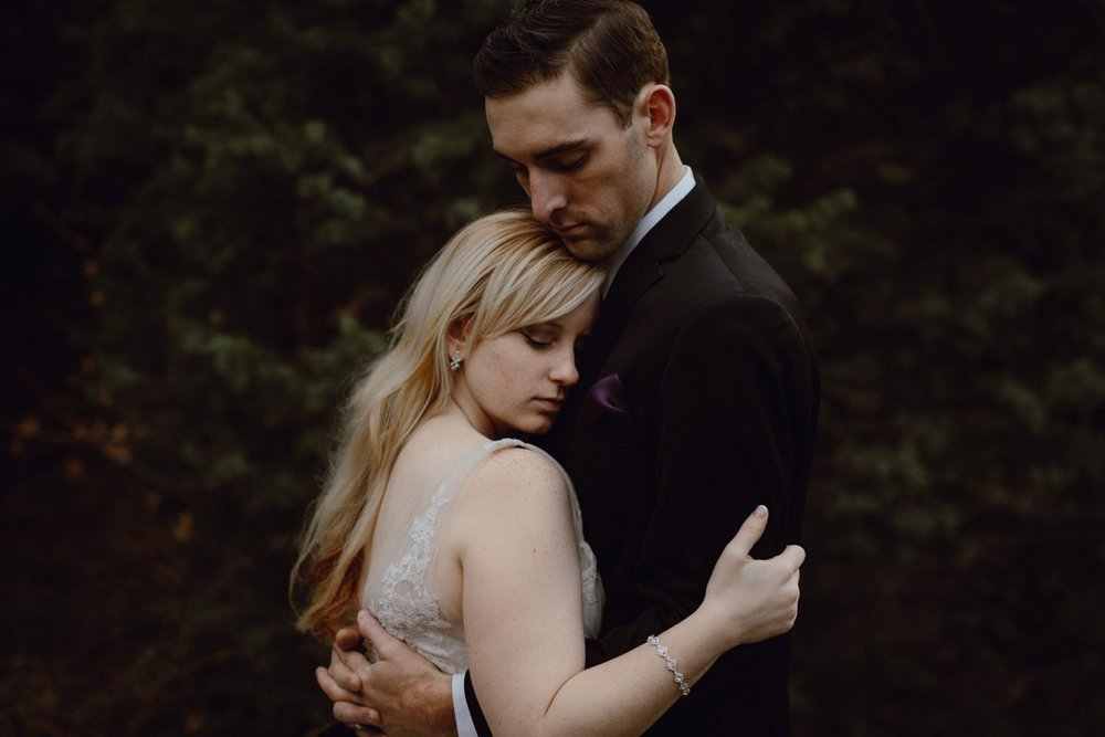A bride and groom embrace during their wedding portraits