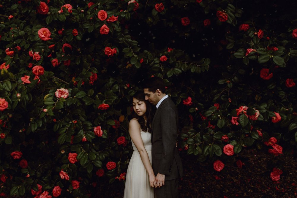 A couple surrounded by red flowers at their Oaks Pioneer Church wedding