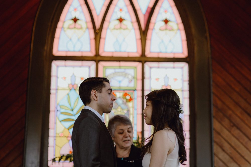 A photo of the bride and groom with the church stained glass in the background at their wedding in Portland OR