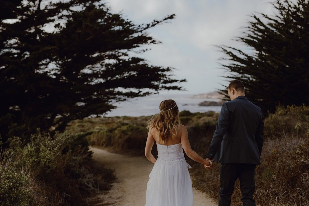 A bride and groom walk together on the beach