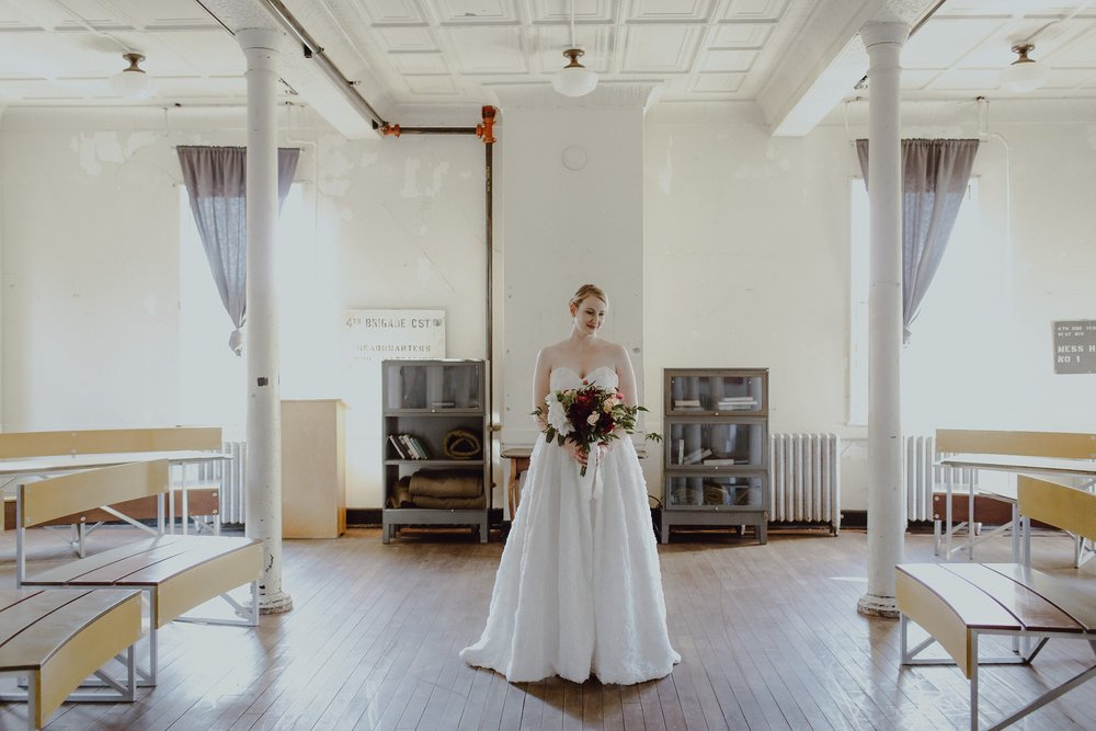 A bride poses with flowers at Headlands Center for the Arts wedding venue