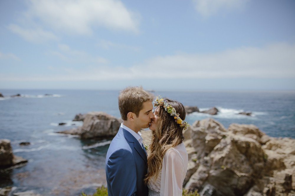 A bride and groom kiss in Big Sur