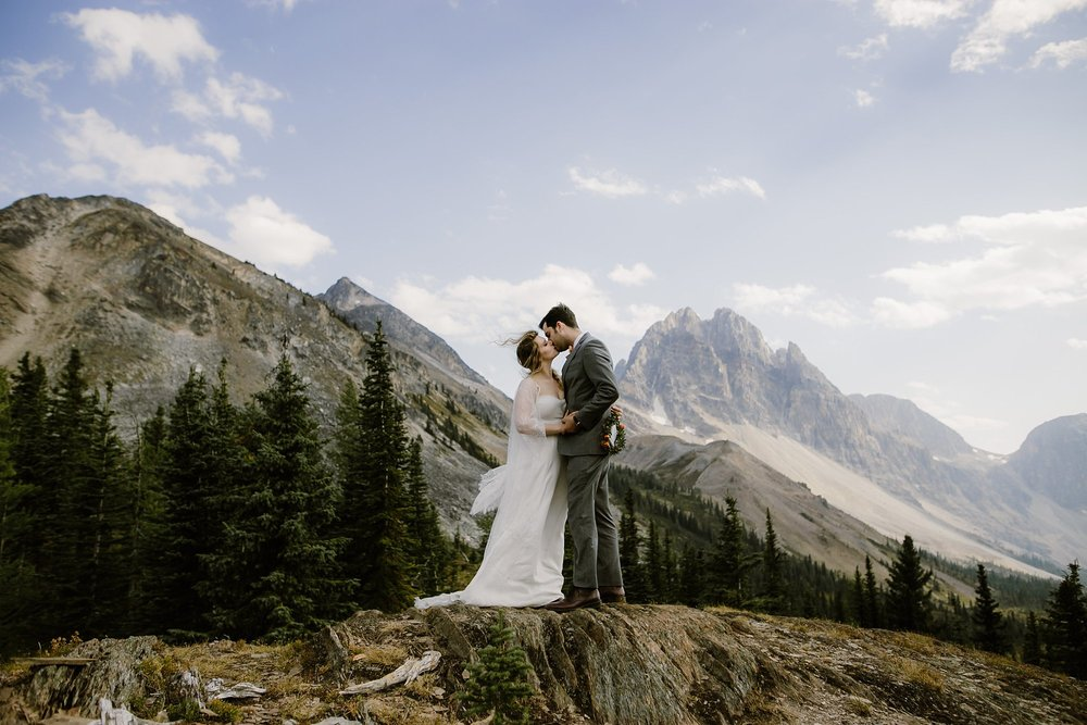 A bride and groom kiss during their helicopter adventure wedding