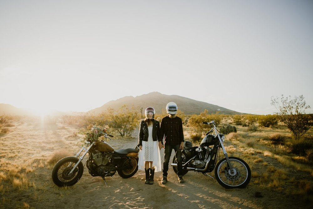 The bride and groom with their motorcycles at their motorcycle elopement