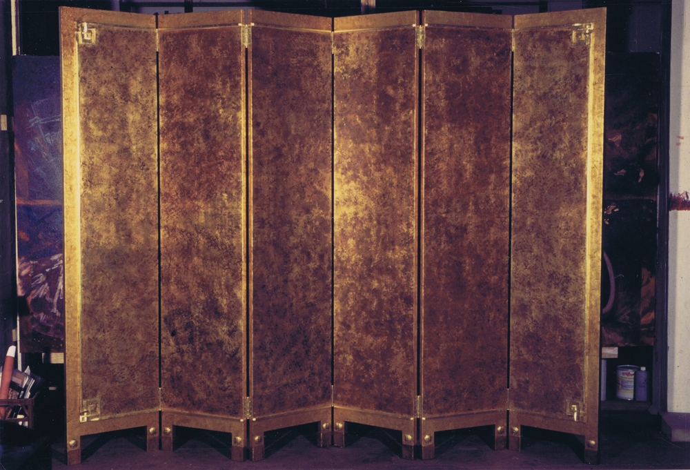 Large gilded & painted screen. Made in collaboration with a team of artists, it features custom made gilded resin corner details & bronzed brass feet. A cracked leaf finish on border and hand printed decorative patterns over chemically oxidised leaf on central area.