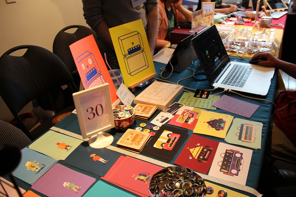 Some wares, images, zines, and postcards for sale at the Bit Bazaar.