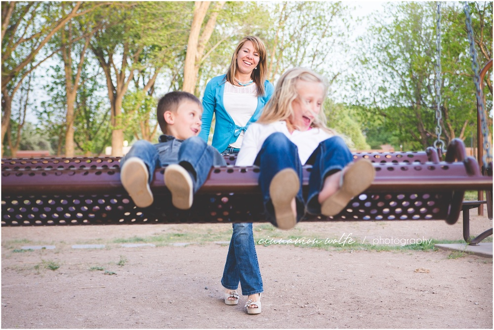 Fun family photo of kids swinging at bachechi open space in albuquerque new mexico